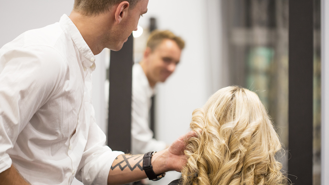 Hairdresser styling woman's hair