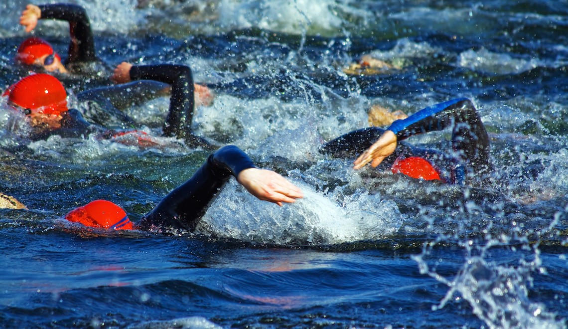 triathlon swimmers competing in the water